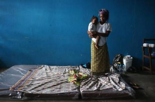 Uma mulher e seu bebê são colocados nos colchões que servem como cama no centro de isolamento./ Foto: Getty Images.